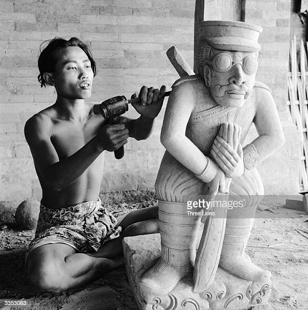 Using a hammer and chisel a Balinese sculptor works on a caricature of a Japanese soldier The Japanese occupied Bali during WW II