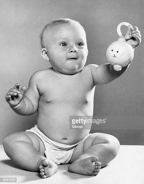 A baby sitting and holding up a rattle with a puppy drawing on it