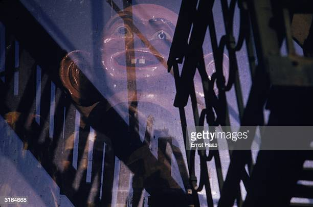 A bizarre effigy with buck teeth and enormous ears amongst the reflections of fire escapes in a New York window
