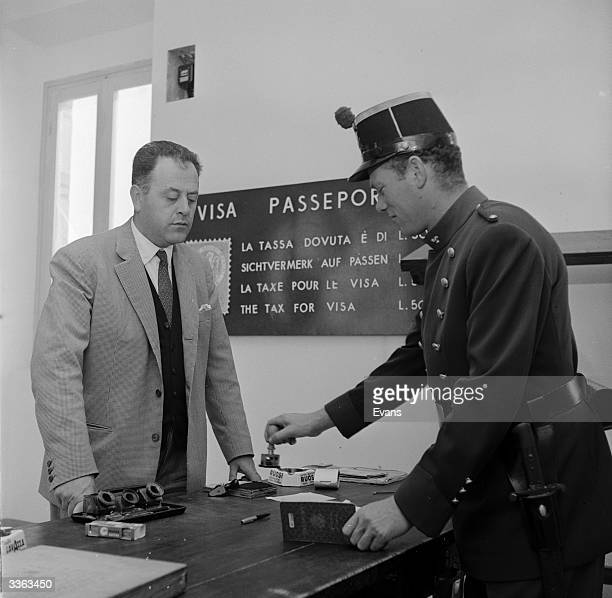 A border guard stamping a visitor's passport as he enters San Marino one of the world's smallest countries