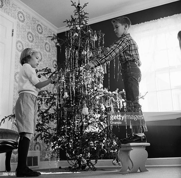 A boy and his sister decorate a Christmas tree with lots of tinsel