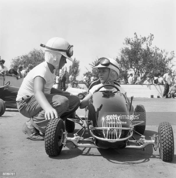 A boy at a quarter midget race crouches down to talk to a fellow boy racer sitting in a derby car They are both wearing helmets and goggles