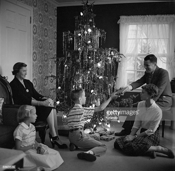 A boy distributes his presents to the rest of the family as they sit round a Christmas tree decorated with lights