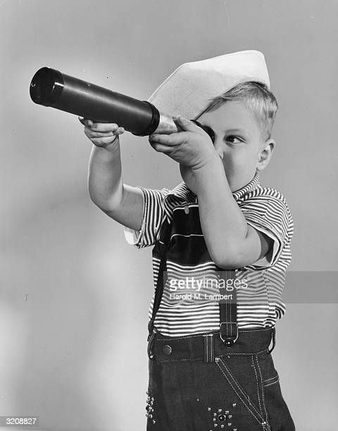 A boy in a sailor's outfit looks through a telescope