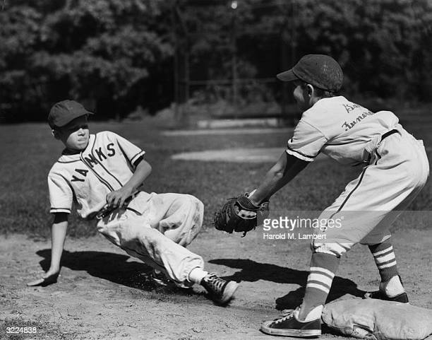 Boy slides toward a base as the defensive player waits to tag him out during a Little League baseball game. They wear team uniforms.