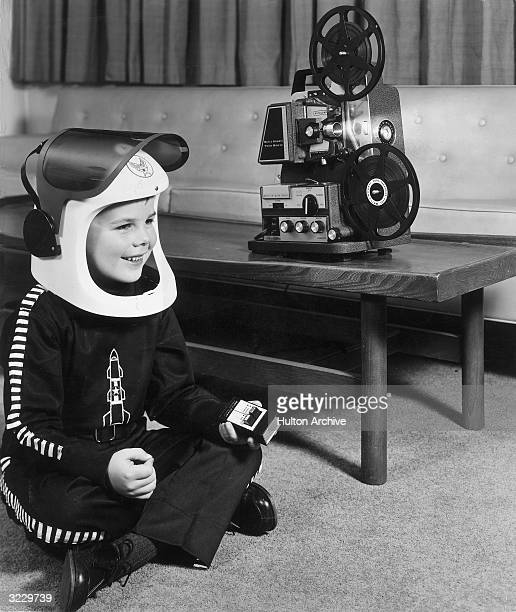 A boy wearing a space helmet and costume watching a film on his Bell Howell Wireless TeleSonic 8mm motion picture projector 1950s He is holding the...