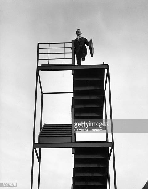 A businessman wearing a suit and carrying a briefcase walks off the top of a staircase that leads to nowhere