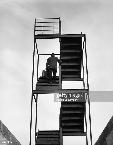 A businessman wearing a suit and carrying a briefcase walks up stairs that lead to nowhere