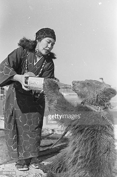 A captive bear drinking from a large bottle held by an Ainu tribeswoman