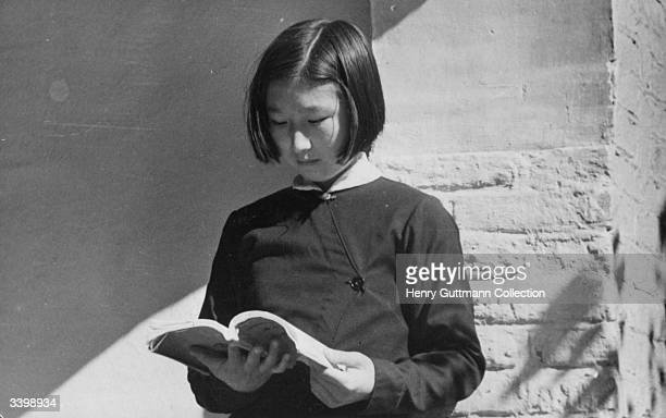 A Chinese Manchu schoolgirl reading a text book