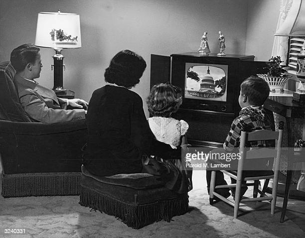 A couple and their daughter and son gather around a television set upon which is an image of the Capitol Dome in Washington DC