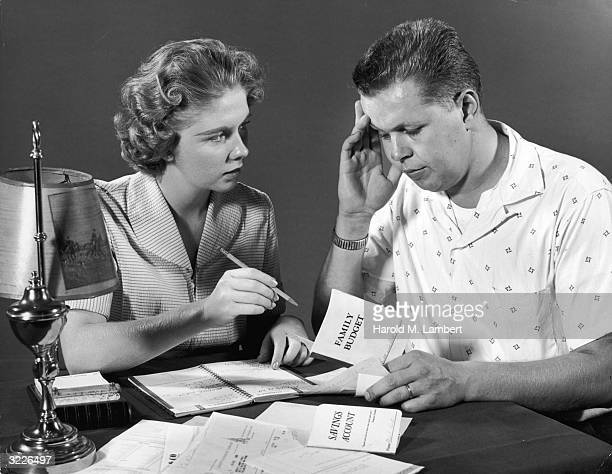 Couple looking worried as they plan their finances at a desk. The man holds his head in his hands as he holds a small Family Budget booklet, as a...