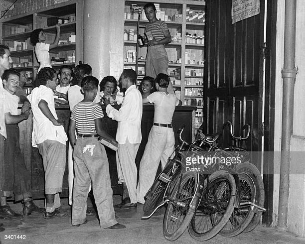 A crowd of delivery boys receiving their orders at the Central Neptune Drugstore in Havana