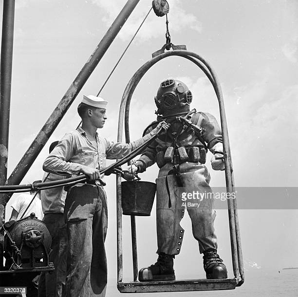 A diver at the US Navy Salvage School at Bayonne New Jersey on the diving 'stage' before going underwater The sailor on the left holds the air and...