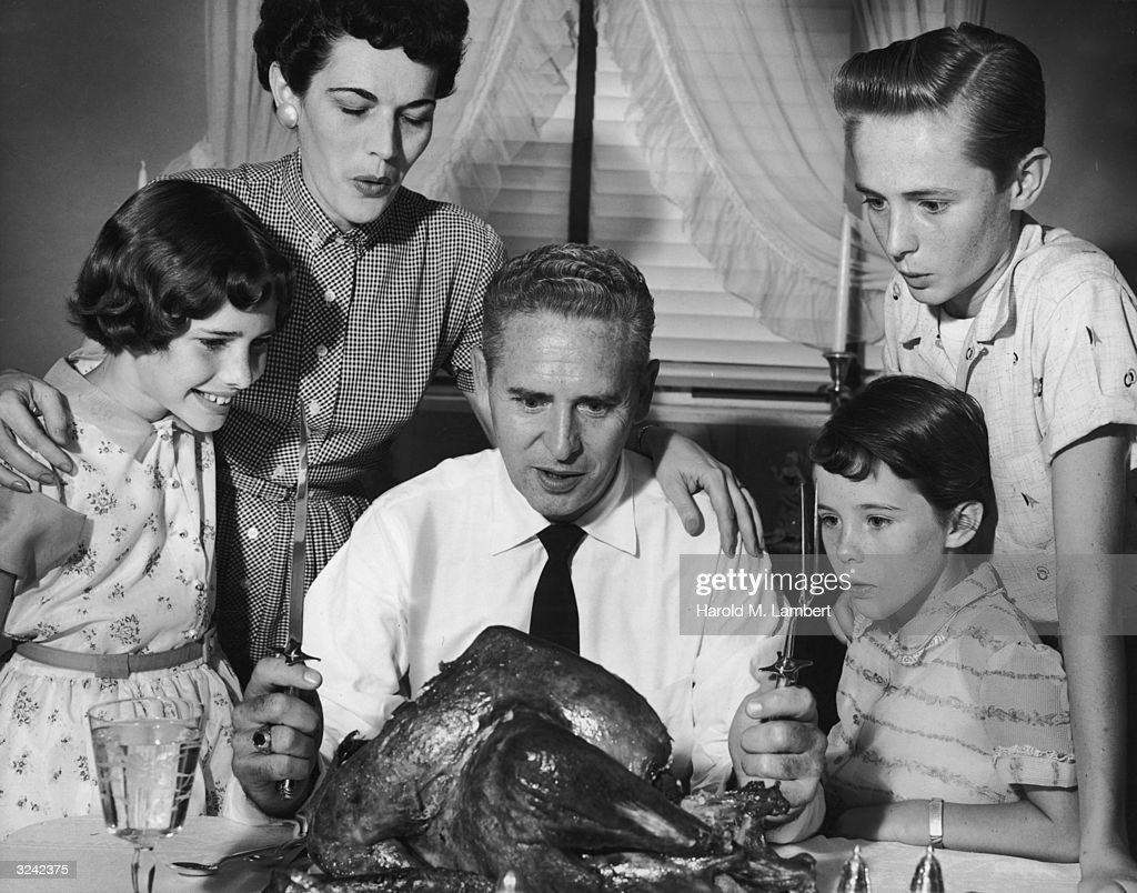A family gathers around a table, watching the father sitting in front of a turkey with carving utensils.