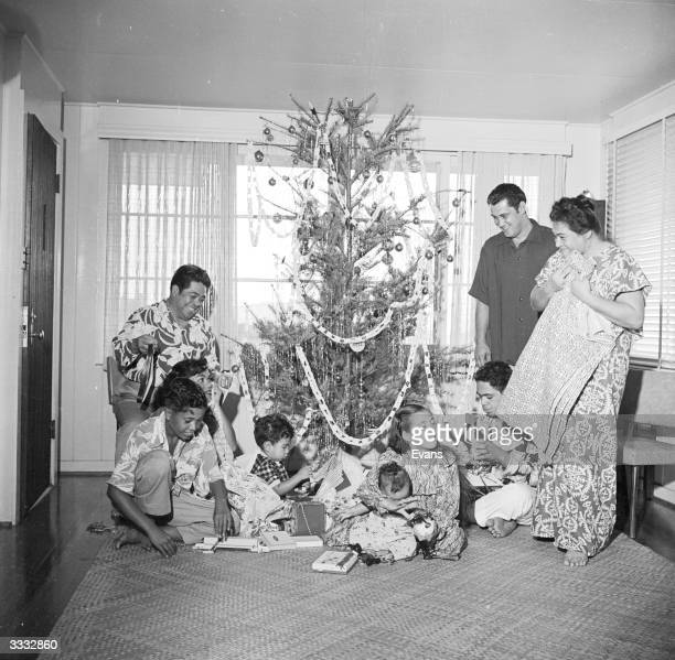 A family in Hawaii gathered around a Christmas tree exchanging gifts on Christmas day