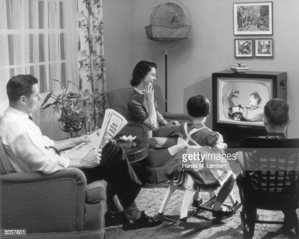 A family sits in their living room watching a children's television program featuring a clown playing with a dinosaur hand puppet The father pauses...