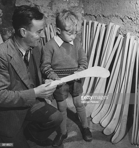 A father showing his young son some hurling sticks at the factory where they are manufactured in Ireland
