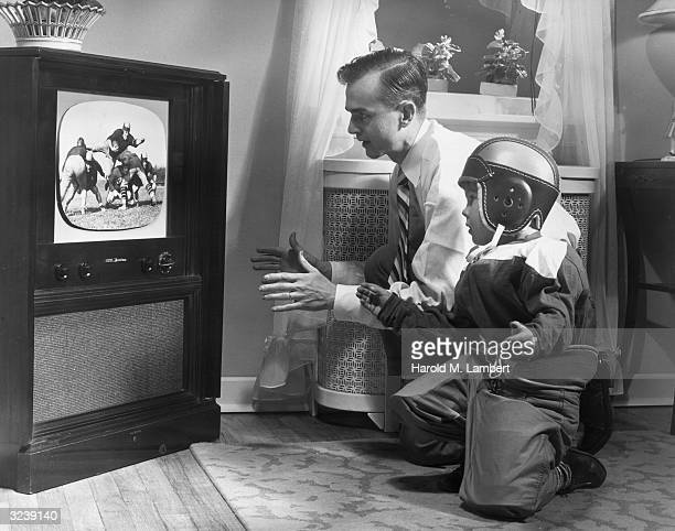 A father watches a football game with his young son who wears a football uniform