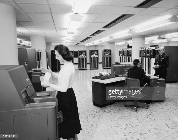 Circa 1955 A female office worker sorts punch cards as two men talk near the console of an IBM 705 III mainframe computer owned by the US Army 1950s