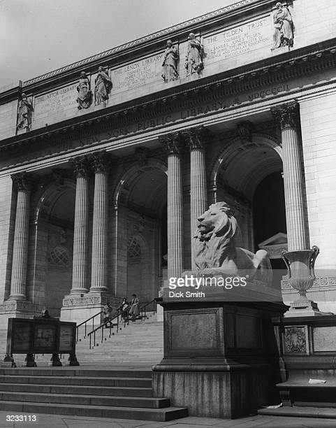 A front exterior view of the New York Public Library Fifth Avenue looking up the front steps with one of the lion statues perched on the front...
