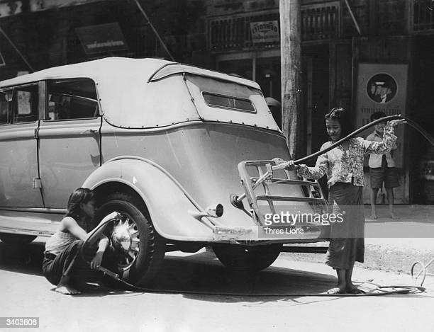 A garage owner's daughter fills a tank and checks the tyres of a car at her father's filling station in Bangkok Thailand