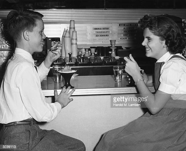 A girl and boy smile at each other while eating ice cream at a soda fountain counter