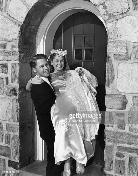A groom smiles while carrying his bride over the threshold of their home She holds the train of her wedding gown