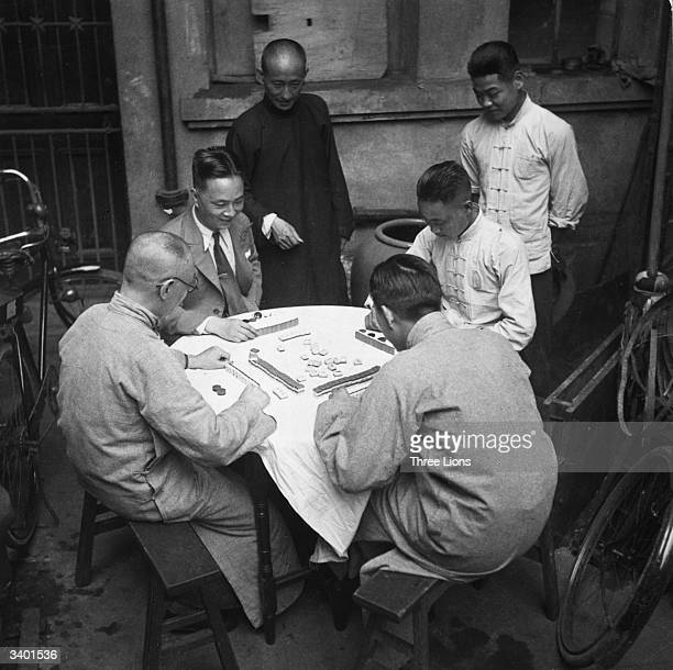 A group of Chinese men sit down to play a game of Mah Jong outdoors