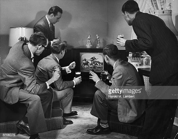 A group of five men sit around a television set watching a football game and holding glasses of beer in a living room