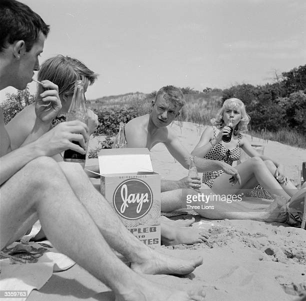 A group of teenagers drinking cola together on West Beach Michigan City Indiana