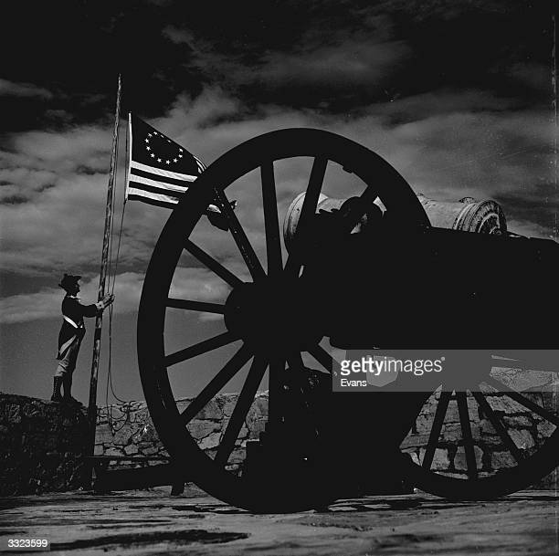 A guard wearing the uniform of a Continental soldier raising the American flag at Fort Ticonderoga where the battle for independence from British...
