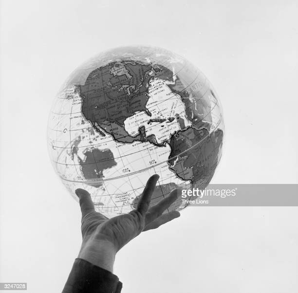 A hand holding a transparent globe made by the Farquhar company of Philadelphia