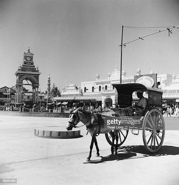 A horse and cart on a street in Mysore Karnataka State southern India The belltower is in the background