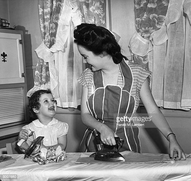Housewife and her young daughter iron clothes side by side on an ironing board.