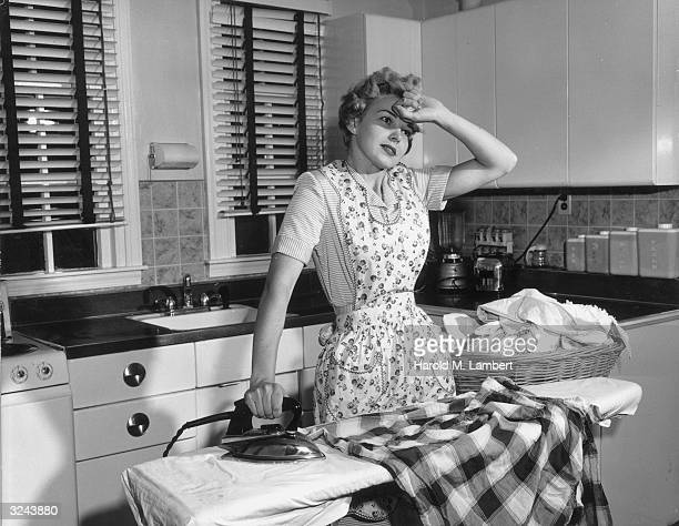 A housewife holds the back of her hand to her forehead while ironing clothes on an ironing board in her kitchen She wears an apron