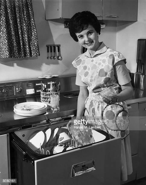 A housewife smiles as she stands by an open automatic dishwasher removing clean glasses She wears a patterned apron A stack of plates and a...