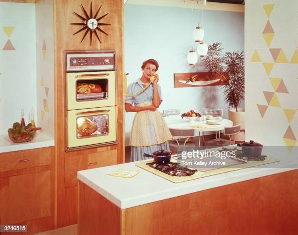 A housewife stands in the kitchen talking on the phone as she stands next to an an oven with a ham and a turkey roasting inside 1950s