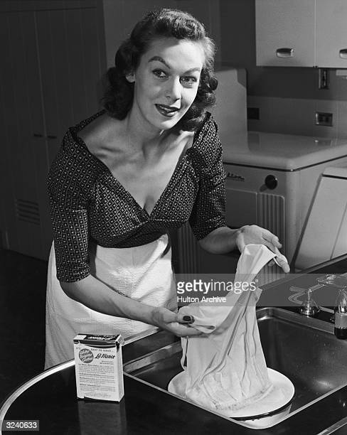 A housewife uses 'La France' bluing compound to whiten linen in a kitchen sink