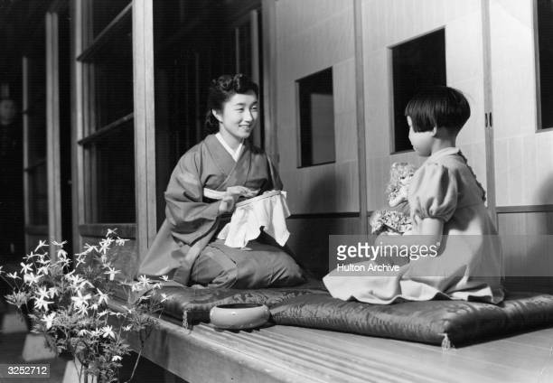 A Japanes woman doing some embroidery while her daughter plays with her doll