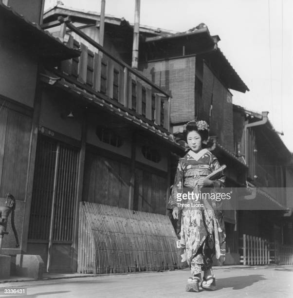 A Japanese girl dressed as a 'Maiko' en route to a party to entertain guests with singing and dancing Her 'Pokkuri' thick wooden clogs are adorned...