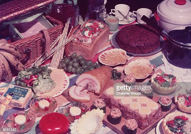 A lavish display of picnic food and a hamper laid out on the grass The treats on offer include cakes salads cold meats and bowls of aspic and a pack...