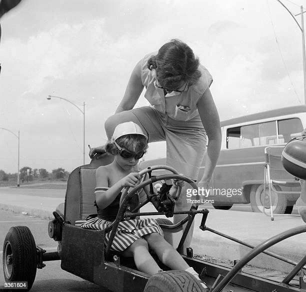 A little girl in a car being given some advice by her mother during 'Grand Prix' races which take place in a parking lot in Livonia Michigan a suburb...