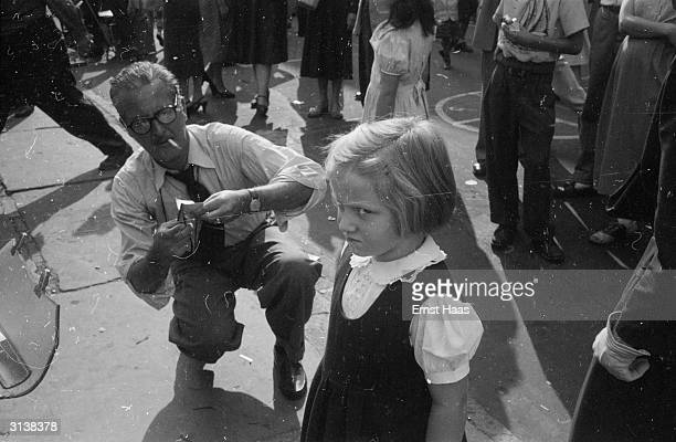 A little girl obviously resents having her silhouette cut out by an artist in Washington Square New York
