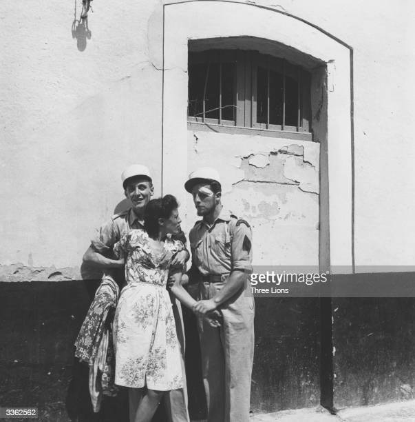 A local girl is arrested by two members of the French Foreign Legion who have their headquarters here in Sidi Bel Abbes Algeria