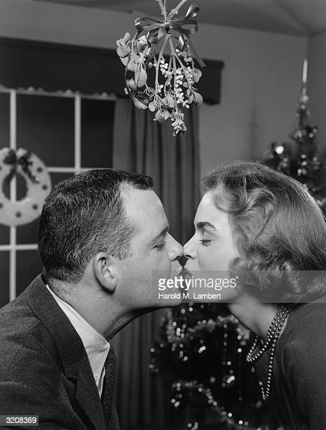 A man and woman kiss under a spring of mistletoe at Christmas