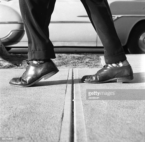 A man avioding the cracks in the pavement as stepping on the lines between paving stones is supposed to bring bad luck