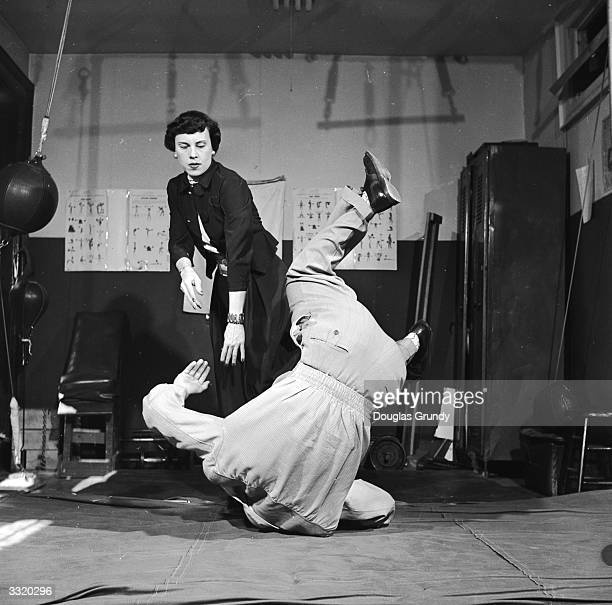 A man is hurled to the floor by a woman in a judo throw