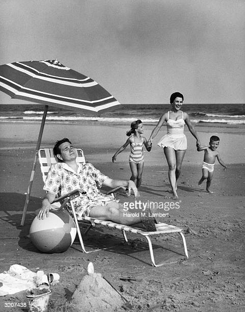 A man lounges in a deck chair under a beach umbrella while a mother runs with their son and daughter on the sand