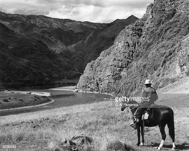 A man sits on horseback looking at the Snake River at Suicide Point trails Hells Canyon National Recreation Area Oregon